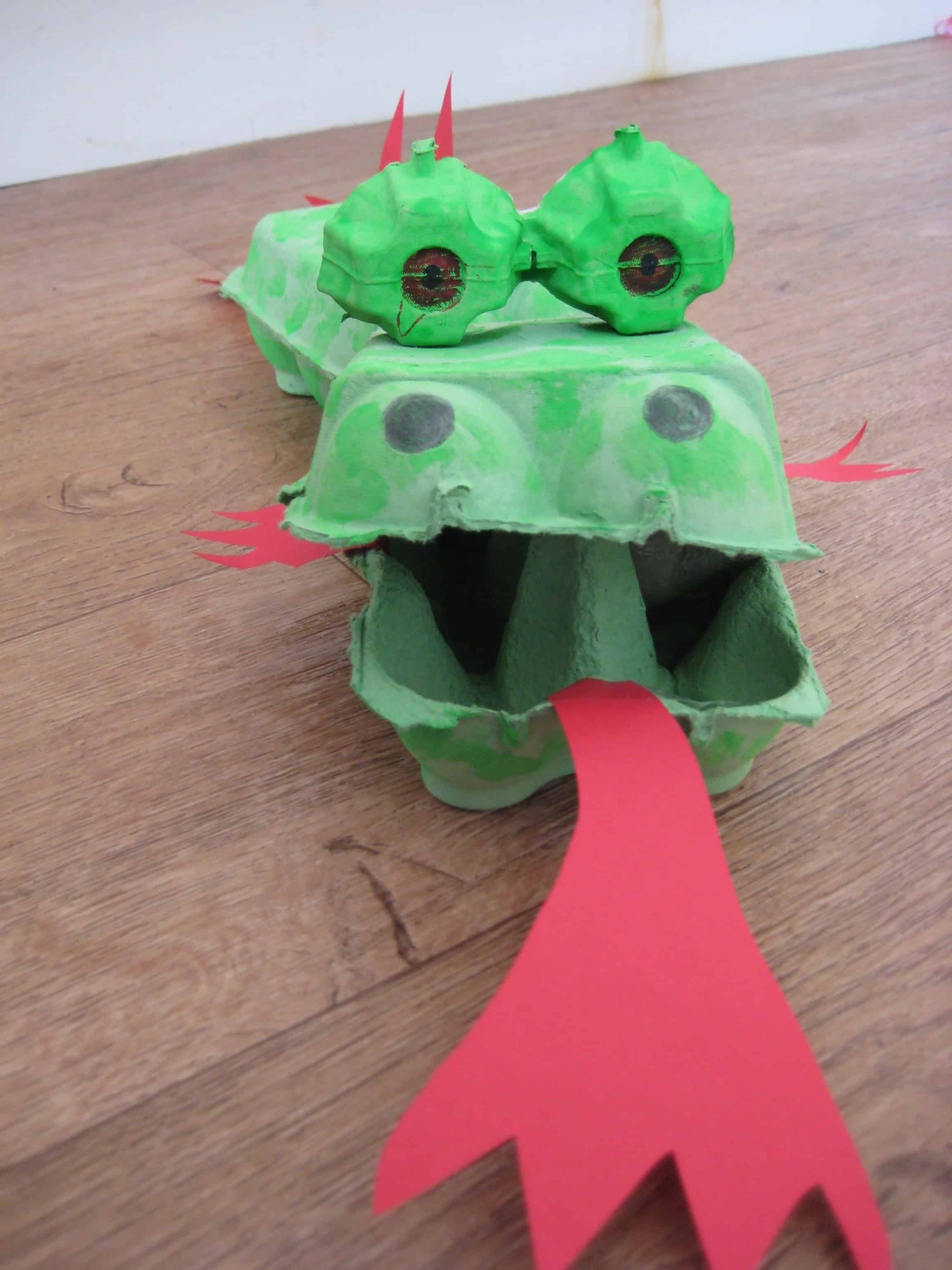 Cut out some flames, spines and a tail from the red paper and fasten ...