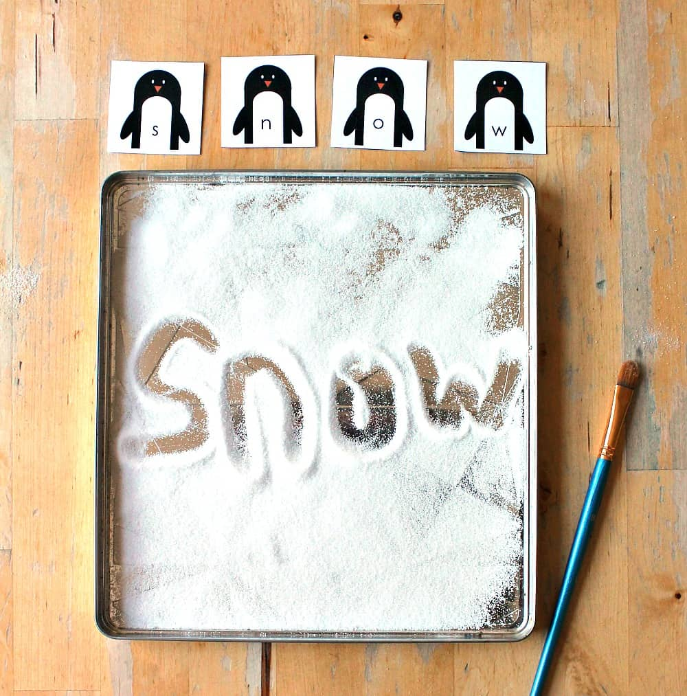 snow writing tray for literacy activity with a penguin theme